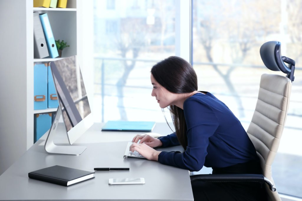 lady with poor posture leaning over office desk to type on her computer keyboard